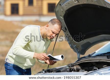 man  broken down car reading   user manual - stock photo