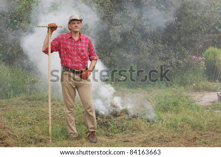 Man burn out dry grass in the garden.Ukraine - stock photo