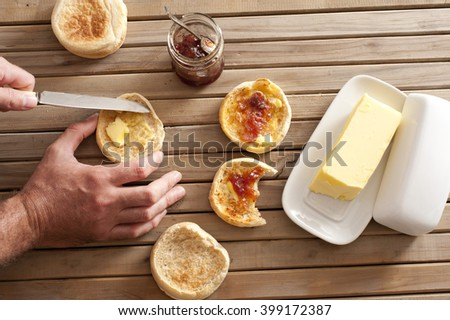 Man buttering a freshly toasted crumpet for breakfast, overhead view of his hands, the crumpets, jam and a pat of farm butter on a slatted wooden table - stock photo