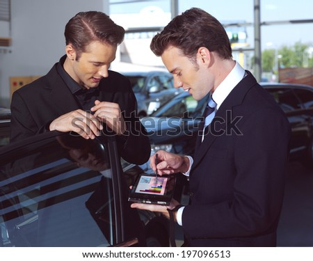 Man buying a car, the salesman talking to him and explaining details on laptop - stock photo
