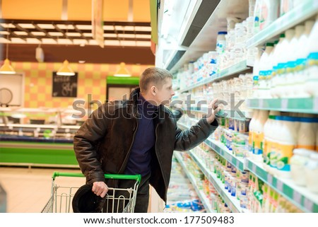 man buys dairy products at the supermarket - stock photo