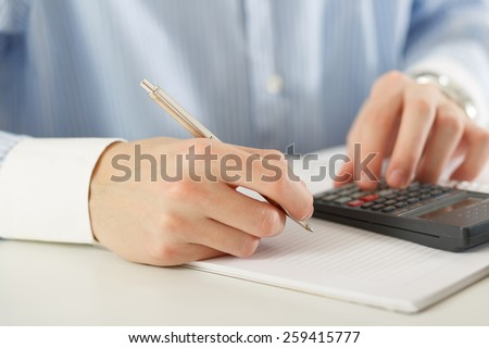 Man calculating and writing  - stock photo