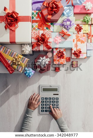 Man calculating costs with a calculator and lots of colorful gift boxes, expensive Christmas concept - stock photo