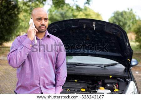 man calling the breakdown service with his car bonnet open - stock photo