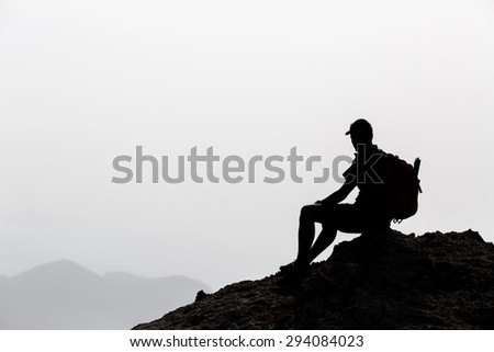 Man camping and hiking silhouette in mountains, accomplish inspiration and motivation concept. Hiker with backpack on top of rocky mountain looking at beautiful inspirational landscape. - stock photo