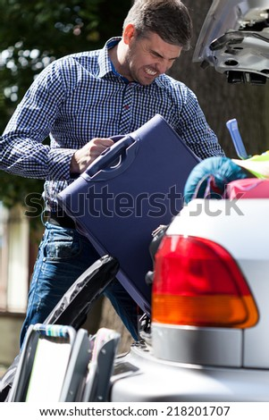 Man can't put luggage into car trunk - stock photo