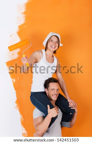 Man carries his girlfriend on his shoulders, while painting - stock photo