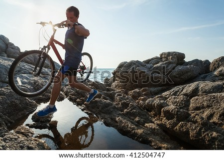 Man carrying a bike on the rock through water - stock photo