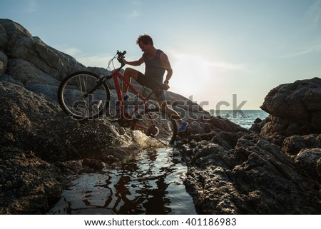 Man carrying a bike on the rock through water during sunset - stock photo