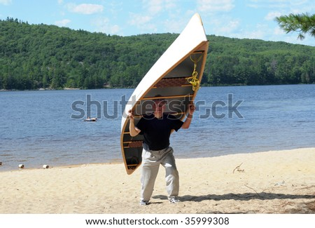 Man carrying a large canoe on a beach - stock photo