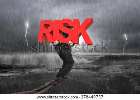 Man carrying big red RISK 3D word walking on old iron chain with dark stormy ocean background - stock photo