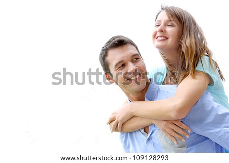Man carrying girlfriend on his back, isolated - stock photo