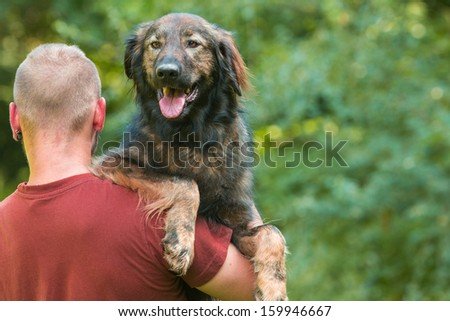 Man carrying his dog - stock photo