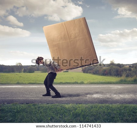 Man carrying on his shoulders a large box - stock photo