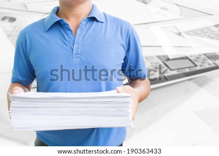 Man Carrying Pile Of Paperwork In Office - stock photo