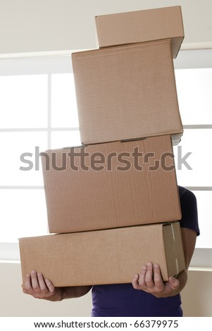 Man Carrying Stacked Boxes on moving day - stock photo