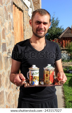 Man carrying two cups of tea - stock photo