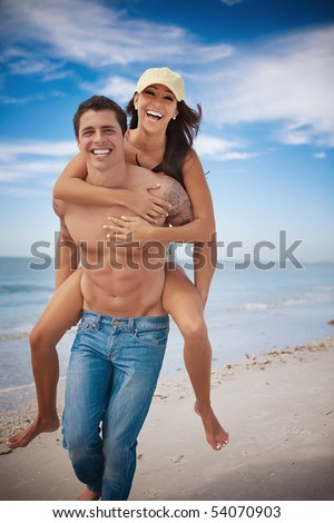 Man carrying woman on a beach, both smiling - stock photo