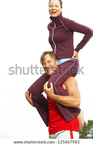 man carrying woman on shoulder outside, white sky visible in the background - stock photo