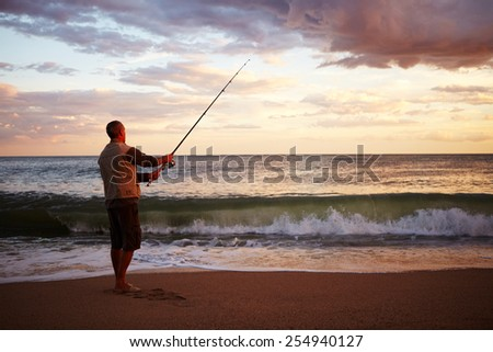 Man casting a fishing line into ealry morning surf - stock photo