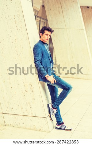 Man Casual Urban Fashion. Wearing blue blazer, patterned under shirt, jeans, fashionable sneakers, a young European college student standing against column outside office building. Instagram effect. - stock photo