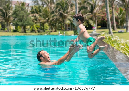 Man catching his son who is jumping into the pool - stock photo