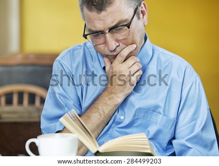 man caucasian reading concentrated in a cafe - stock photo