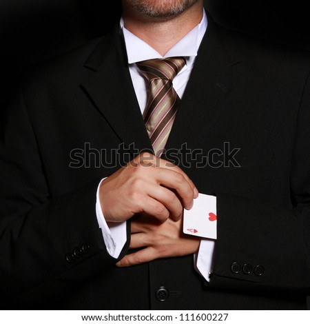 man cheating with playing cards - stock photo