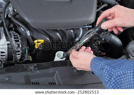 Man Checking Antifreeze in a Car coolant System - stock photo