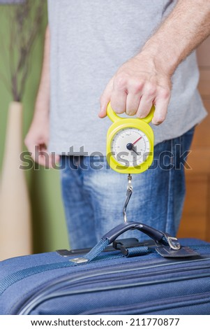 Man checking hand luggage weight using a steelyard balance by low cost airlines restrictions - stock photo