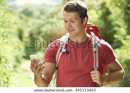 Man Checking Location With Mobile Phone On Hike - stock photo