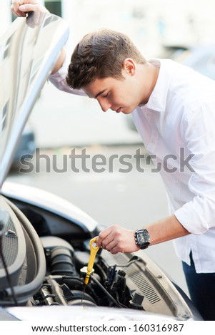 Man checking oil level in car  - stock photo