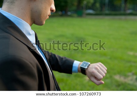 Man checking the time in the park - stock photo