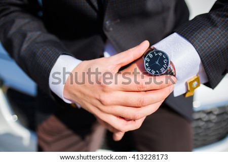 Man checking the time on his wrist watch - stock photo