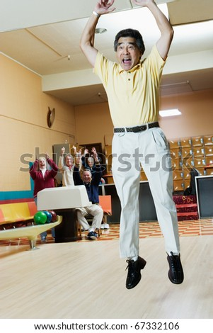 Man cheering at bowling alley - stock photo