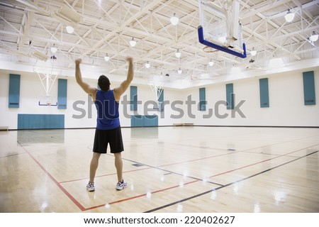 Man cheering on basketball court - stock photo