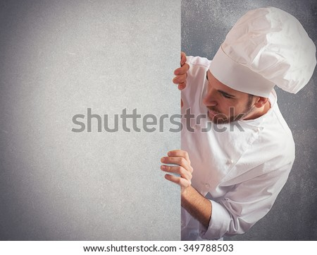 Man chef looks at a big billboard - stock photo