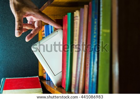 man choose ebook among paper books. new technology concept - stock photo