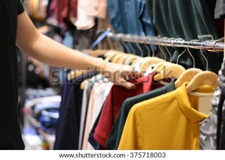 Man chooses  clothes in the clothing store - stock photo