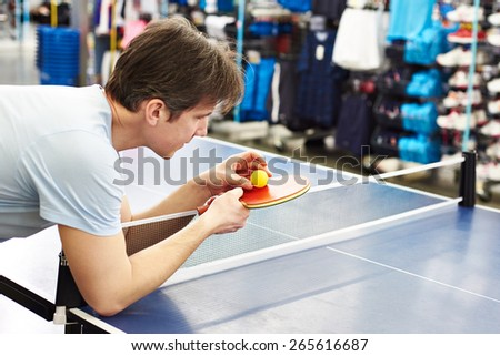 Man chooses table tennis racquet in sport shop - stock photo