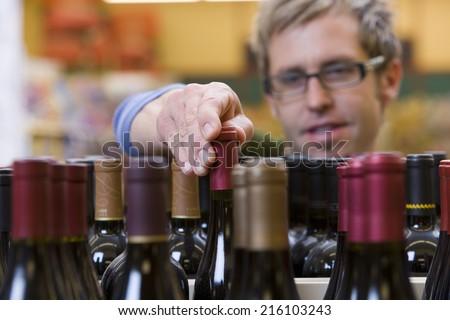 Man choosing a bottle of wine - stock photo