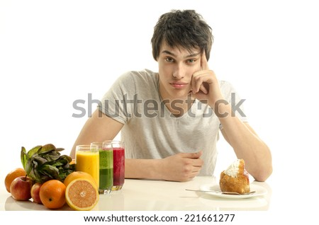 Man choosing between fruits, smoothie,salad and organic healthy food against sweets, sugar, lots of candies - stock photo