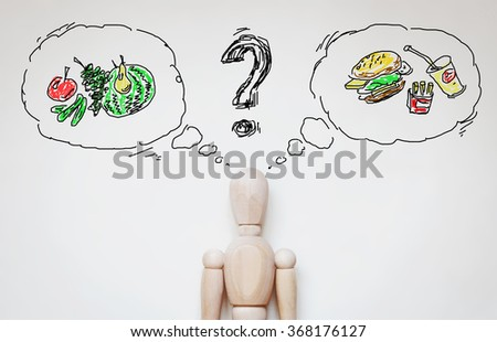 Man choosing healthy food. Abstract image with wooden puppet - stock photo