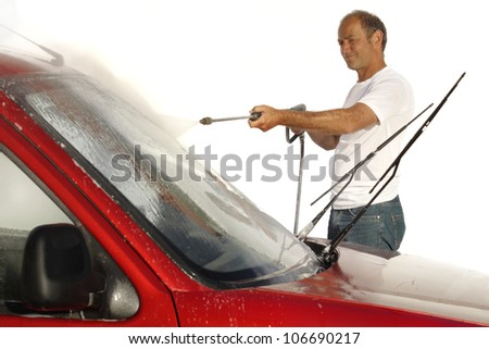 Man cleaning car with high pressure water blaster - stock photo