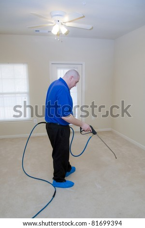 Man cleaning carpet with commercial cleaning equipment, during a pre-treat for stain removal - stock photo