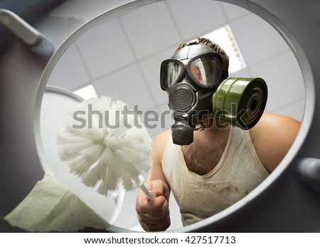 Man cleaning the toilet bowl - stock photo