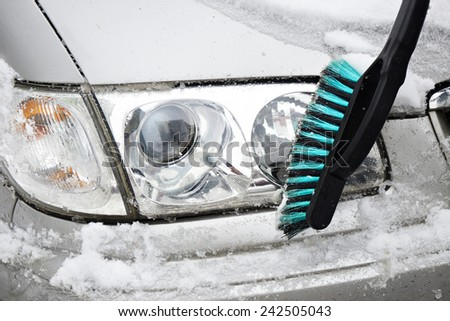 Man cleans a car from the snow with a brush - stock photo