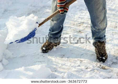 man cleans the track from snow shoveling, sunny winter day - stock photo