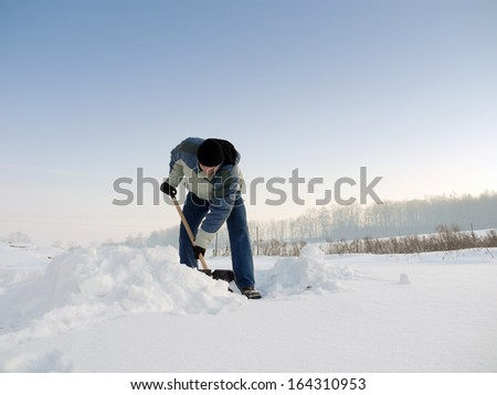 Man clearing his backyard with shovel after heavy snowfall - stock photo
