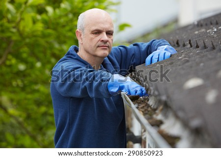 Man Clearing Leaves From Guttering Of House - stock photo